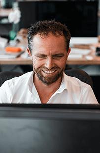 Fred lachend achter zijn computer
